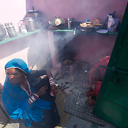 Cooking food or chai (spiced India tea) in a traditional kitchen of a low-income family. Often firewood or cowdung are used as fuel, which - if a chimney is absent - causes health problems due to a lot of smoke inhaled.