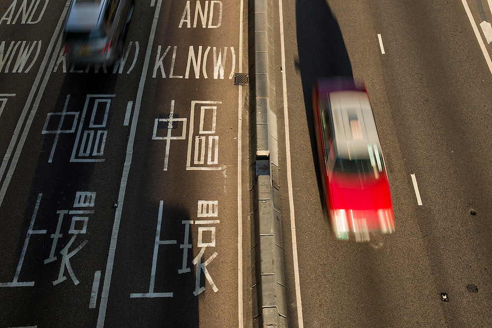 China, Hong Kong, Overview of red taxi speeding along Connaught Road on winter morning