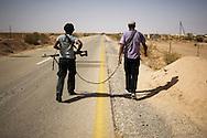 LIBYAN ARAB JAMAHIRIYA, Um al Far : Libyan rebel fighters walk on a road near Um al Far after they took control of the village, on July 28, 2011. ALESSIO ROMENZI