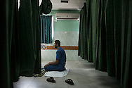Gaza Strip, Beit Lahia: A male nurse prays inside the Beit Lahia hospital emergency room on August 10, 2012. ALESSIO ROMENZI