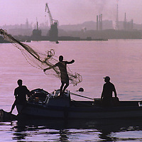 A petrol refinery is seen in the distance as a fisherman casts his net in the early morning in Havana, Cuba.