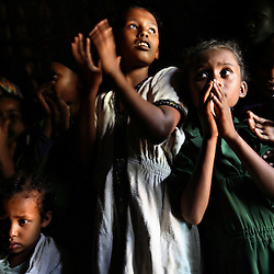 Children sing and clap at the wedding of Tsegaya Mekonen, 13, and Talema Meseret, 23 in Yeganda Village, Amhara Region, Ethiopia on May 20, 2007. The practice of early marriage remains widespread in Ethiopia, especially in the northern Amhara and Tigray regions, where parents consent to their daughters' consummated marriages when they are still as young as 10 or 12. In Amhara, 50 percent of girls are married by the age of 15, despite the enactment in 2000 of the revised Family Law, which sets the legal age for marriage at 18.