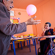2015 April&mdash;Zaatari camp for Syrian refugees, Jordan. UNICEF School One/Bahrain School. Against all odds, Khalid, 7, from Daraa, Syria, is the top student in his first grade class. This fortitudinous young man lost his mother at age three, he has been separated from his father for over two years by war, and he is physically disabled with muscular dystrophy. Khalid and his stepmother, Dilal, fled to Jordan for what they thought would be about a month stay, until the war quieted down. Due to the continued unrest in Syria they have lived in Zaatari camp for over two years.  <br /> <br /> Khalid is having one on one instruction in the Mercy Corps resource room. His volunteer instructor, Ibrahim (also a refugee), has over 35 years of teaching experience in Syria.