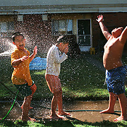 Boys use a garden hose to cool off outside their apartments in Sacramento, CA on June 22, 1999. From left to right are Peter Le, 9, Phong Tang, 8, Thai Do, 8, and Eric Le, 10.