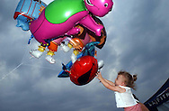 NORTH BRUNSWICK NJ - Two-year-old Gabriella Socio tries her best  to grab Elmo from the helium balloons, as she tours the Carnevale Italiano on her mother's arms.  She got away with Barney.           (Photo By Miguel Juárez Lugo)