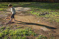 """So, what is it you like about mud?  """"Ahh...pretty much everything.""""  -Five year old Ryley Macleod plays in a puddle adjacent to his house on Maggie Street in Calistoga."""