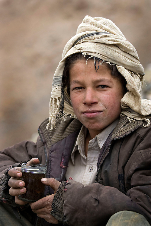 A young boy works alongside emerald miners high in the mountains of the Panjshir, Afghanistan on the 15th December 2008.