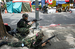 A young man lies dead in the background within the Red-shirt camp, killled during military crackdown to end the Red-shirt protests.