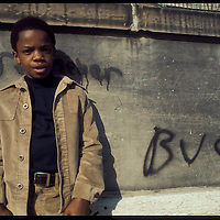 Child in Cincinnati, Ohio stands against a wall next to graffiti in the 1970s.