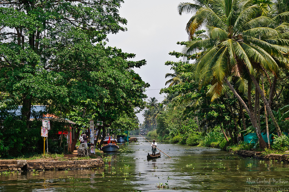 A man navigates the Kerala Backwaters by boat and pole.