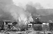gbs020380a/ASEC/Greg Sorber -- A National Guard helicopter flies over a burning New Mexico Penitentary near Santa Fe during the riot in 1980.