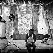 The number of cholera victims in CitÈ Soleil, a slum of Port-au-Prince, is increasing day by day exponentially, according to a doctor of Doctors Without Borders./// An employee from Doctors Without Borders decontaminates with a chlorine solution a man coming from Cite Soleil and affected by cholera, at the Sarthe hospital in Port-au-Prince.