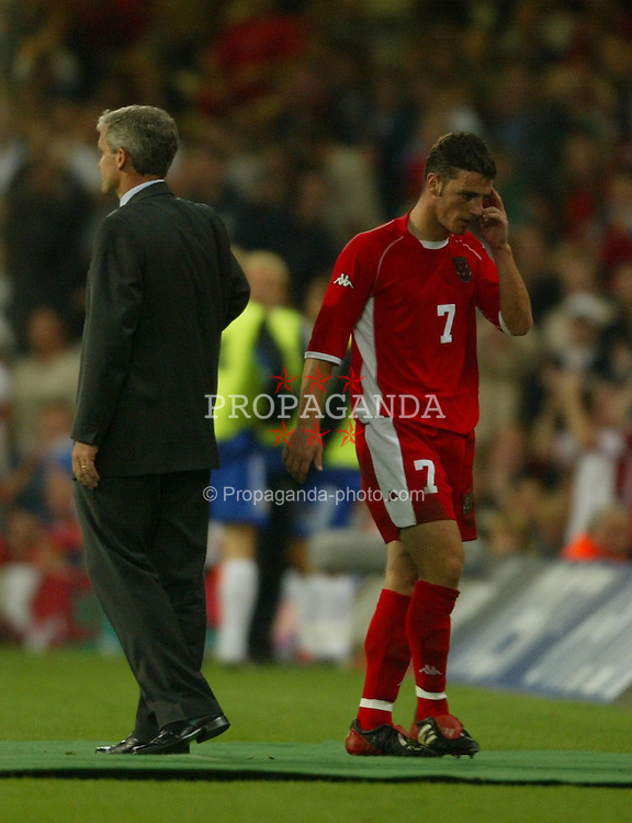 CARDIFF, WALES - Wednesday, September 10, 2003: Wales' Jason Koumas walks past manager Mark Hughes after being sent off against Finland during the Euro 2004 qualifying match at the Millennium Stadium.. (Photo by David Rawcliffe/Propaganda)