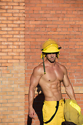 muscular fireman without a shirt outdoors