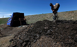 A picture made available on 05 July 2012 of a Mongolian miner emptying a container of coal at a coal mine in the mining town of Nalaikh in Mongolia, 01 July 2012. Once a thriving mining town, Nalaikh is one of first and oldest mining site in Mongolia but has seen a decline in its fortune as mining disasters and accidents plague the site. With little government oversight, only a handful of small companies and informal miners work on the site with scant regard to safety standards. Mongolia is rich in a variety of natural resources including forests, coal, iron ore, gold and copper. Expansion of the mining industry has turned the sector into the most important income source and led to an economic growth rate last year of around 17 per cent. The majority of raw materials are exported to China. Seeking to to reduce the dependency on China for exports and Russian imports, Mongolia has embarked on a policy of closer economic ties with other countries such as Germany, Canada and the United States. Despite impressive growth rates, about one-third of the population lives below the poverty line while unemployment and inflation are high.