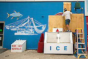 Bowie Seafood owner Don Crum places plywood over the windows of his business during preparation for Hurricane Matthew, Wednesday, Oct. 5, 2016, on Tybee Island, Ga. (AP Photo/Stephen B. Morton)