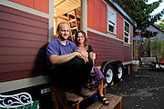 Kol Peterson, left, and Deb Delman sit outside one of the three tiny houses at their recently-opened hotel in Northeast Portland. Caravan – the Tiny House Hotel comprises of three small structures ranging in size from 90 to 160 square feet, all of which rent for $125 per night.