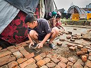 05 AUGUST 2015 - KATHMANDU, NEPAL: A couple puts in a brick patio in front of their tent in a large Internal Displaced Person (IDP) Camp in the center of Kathmandu. The camp is next to one the most expensive international hotels in Kathmandu. More than 7,100 people displaced by the Nepal earthquake in April live in 1,800 tents spread across the space of three football fields. There is no electricity in the camp. International NGOs provide water and dug latrines on the edge of the camp but the domestic waste water, from people doing laundry or dishes, runs between the tents. Most of the ground in the camp is muddy from the running water and frequent rain. Most of the camp's residents come from the mountains in northern Nepal, 8 - 12 hours from Kathmandu. The residents don't get rations or food assistance so every day many of them walk the streets of Kathmandu looking for day work.      PHOTO BY JACK KURTZ