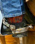 The boots, spurs, and chaps are functional pieces of equipment used every day by the American cowboy. As well as being functional they can be quite decorative and the spurs are often inlayed with silver or gold. This cowboy proudly wears gold and silver inlayed trophy spurs he won as a team roper.
