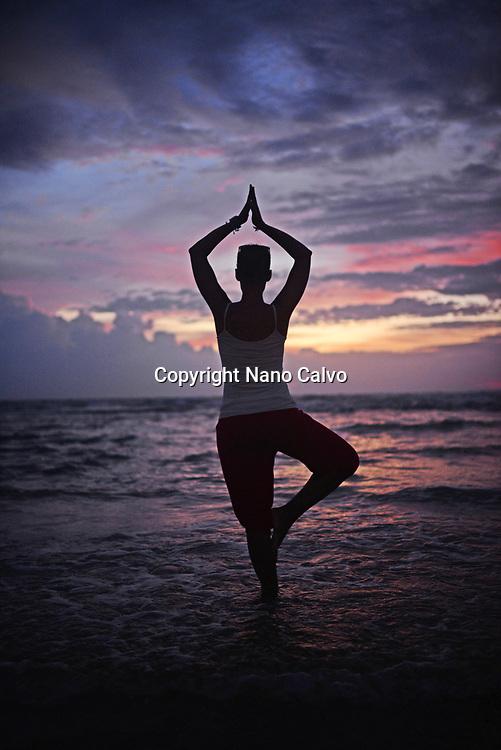 Young woman doing yoga tree pose at sunset,  Hikkaduwa beach, Sri Lanka