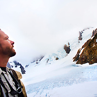 Photojournalist James Branaman looks out at the Blue Glacier on Mt. Olympus, seen from the lateral moraine.The Hoh River trail in Olympic National Park starts in the mossy and lush Hoh Rain Forest. From there you climb over 5,000 ft. in elevation along towering trees and rock to overlook the windswept Blue Glacier on Mt. Olympus. Tracing your steps back to the Hoh River visitors center the hike covers over 36 miles of diverse climate and ecosystems ranging from temperate rain forest to alpine.