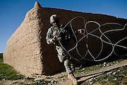Specialist Juan Gil, of the 82nd Airborne, strings concertina wire as part of security precautions for a shura, or community meeting, in Chenar, Kandahar province, Afghanistan that involved local Afghans, US military, Afghan governing officials, and NATO leaders on Thursday, March 22, 2007.