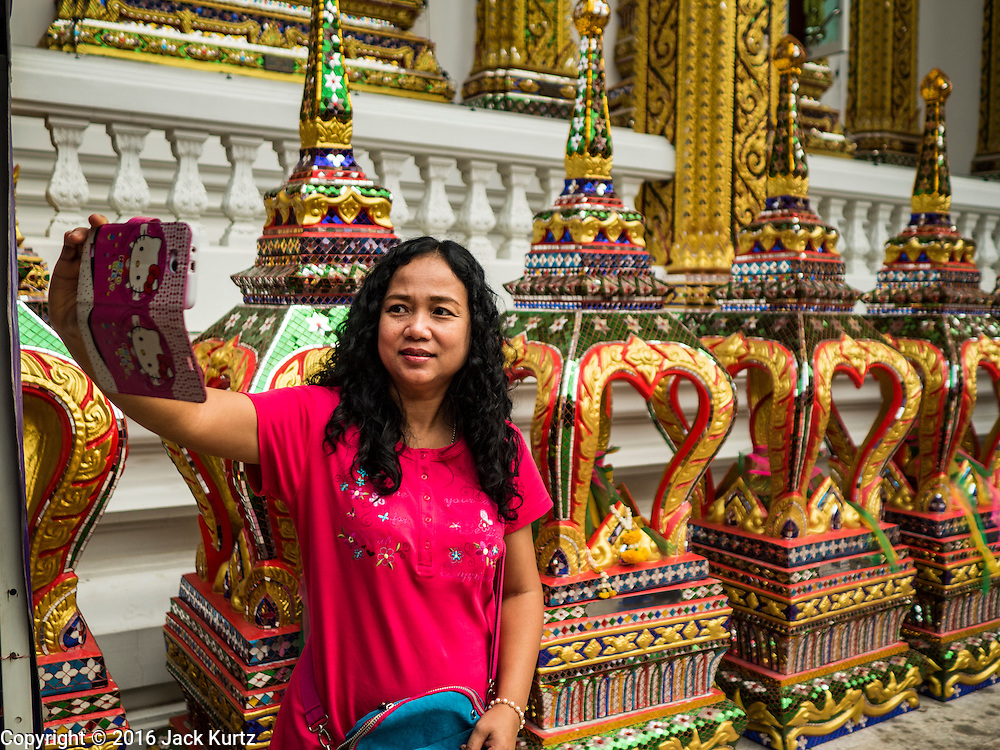 30 JANUARY 2016 - NONTHABURI, NONTHABURI, THAILAND: A woman takes selfie after she made merit by leaving blessed scarves at Wat Bua Khwan, a large Buddhist temple in Nonthaburi, north of Bangkok, Thailand.        PHOTO BY JACK KURTZ