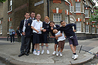 Mixed age group of children posing in the street on way home from school.