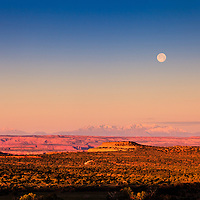 The full moon sets at sunrise over Utah's Canyonlands National Park and the Green River plateau, with Mount Pennell and Capitol Reef National Park in the distant background. WATERMARKS WILL NOT APPEAR ON PRINTS OR LICENSED IMAGES.