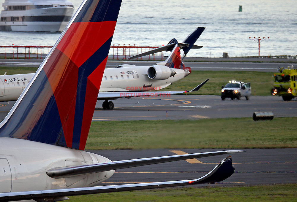 A Delta Conection jet's tail is seen mangled after it was struck by a Delta 767 airliner this evening at Logan  Staff Photo by Mark Garfinkel  .