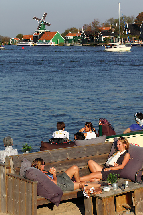People enjoy the sun opposite the windmills of Zaanse Schans, just north of Amsterdam