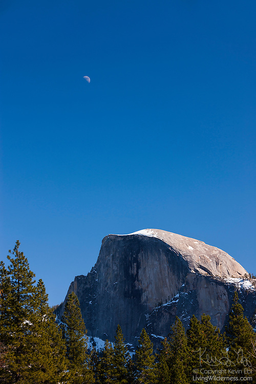 A half moon, technically known as the first quarter moon, rises in the sky above Half Dome in Yosemite National Park, California. Half Dome, 8836 feet (2693 meters) tall, is a granite dome that seems to be missing a large section. While named Half Dome, the missing piece is likely a quarter, rather than half. Scientists also believe the missing granite also eroded away as fast as it was exposed, rather than falling off in a dramatic event.