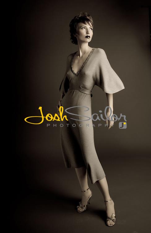 Elegant fashion model on dark sweep wearing a flowing gown.