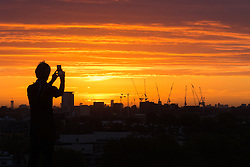 Primrose Hill, London, September 27th 2016. A man photographs the sunrise on Primrose Hill as dawn breaks over London. &copy;Paul Davey<br /> FOR LICENCING CONTACT: Paul Davey +44 (0) 7966 016 296 paul@pauldaveycreative.co.uk