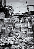 Two sisters seek among the pile of garbage that covers part of the graves in search of material for recycling in exchange for a few pesos ,to buy some food.