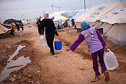 Syrian refugees carry supplies of water past tents at the Za'atri Syrian refugee camp in northern Jordan February 5,2013. ..Jordan announced on Tuesday that the number of Syrian refugees in the country is expected to exceed 700, 000 in 2013, the state-run Petra news agency reported. (Photo by Heidi Levine/Sipa Press).