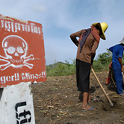 Rural Cambodia farmers work a piece of land that has been marked for landmine near Pailin, Cambodia.
