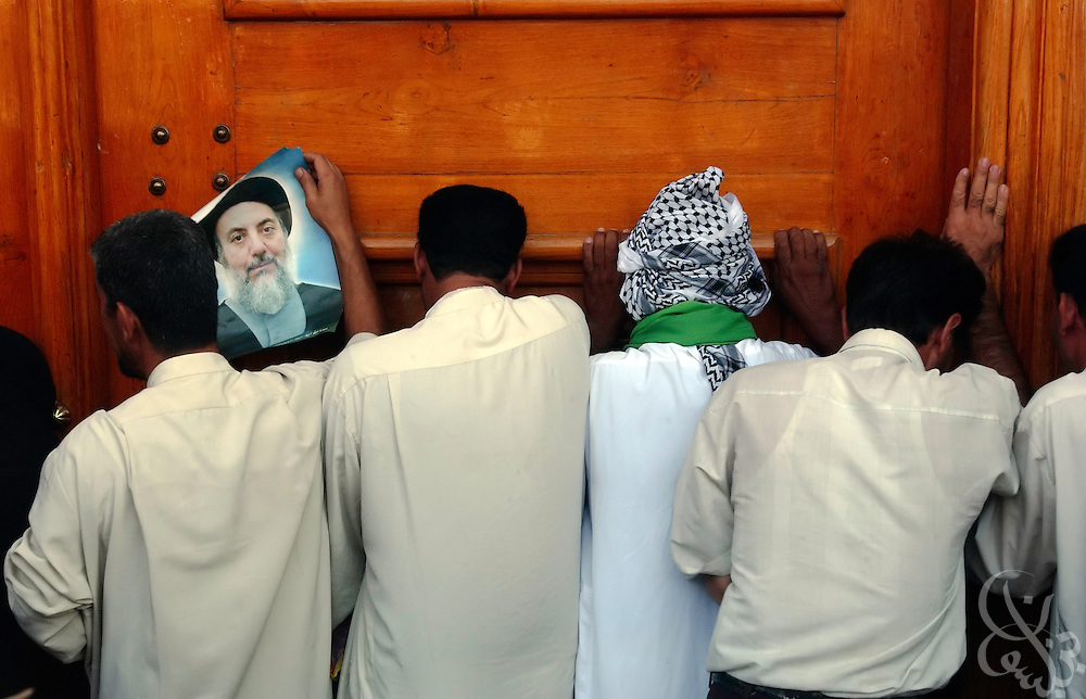 An Iraqi Shiite mourner holds a picture of slain cleric, Mohammed Baqir al-Hakim, as he and others cry against a wooden doorway of the Imam Ali shrine August 30, 2003 in Najaf, Iraq. The shrine, Iraq's holiest, was the scene of a massive car bomb Aug. 29, 2003 that killed al-Hakim and more than a hundred people following Friday prayers.