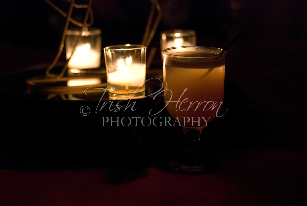 Candlelight illuminates a mixed drink.