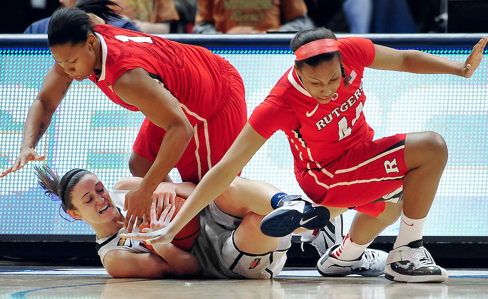 Connecticut's Kelly Faris, bottom, holds possession of the ball while pressured by Rutgers' Khadijah Rushdan, top left, and Betnijah Laney, right, in the first half of an NCAA college basketball game in the quarterfinals of the Big East women's tournament in Hartford, Conn., Sunday, March 4, 2012. (AP Photo/Jessica Hill)