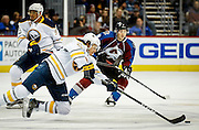SHOT 2/25/17 9:24:08 PM - The Buffalo Sabres' Sam Reinhart #23 tries to get a pass off to a teammate while falling to the ice against the Colorado Avalanche during their NHL regular season game at the Pepsi Center in Denver, Co. The Avalanche won the game 5-3. (Photo by Marc Piscotty / © 2017)