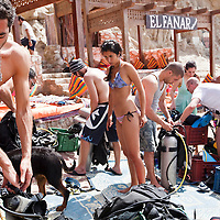 "A group of divers prepares their equipment before entering the Blue Hole outside of Dahab, Egypt. The Blue Hole is notorious for the number of diving fatalities which have occurred there, earning it the sobriquet ""World's Most Dangerous Dive Site"" and the nickname ""Diver's Cemetery"". The site is signposted by a sign that says ""Blue hole: Easy entry"". Accidents are frequently caused when divers attempt to find the tunnel through the reef (known as ""The Arch"") connecting the Blue Hole and open water at about 52 m depth. According to dive experts roughly 10 people die each year. April 2012."