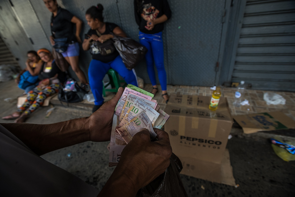 CARACAS, VENEZUELA - JANUARY 15, 2015: Vendors illegally sell blackmarket butter, soap and cooking oil outside of the Quinto Crespo government market for over five times the price of each item set by government price controls. Despite being a petro-state with one of the largest oil reserves in the world, basic food goods such as cooking oil, milk, chicken, coffee, rice, sugar and corn meal are difficult to find in stores across Venezuela.