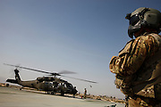 A door gunner waits at the FOB Kunduz while his Back Hawk helicopter is refueled.