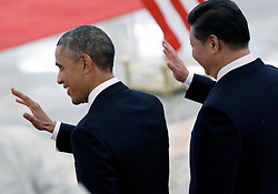 epaselect epa04485881 US President Barack Obama (L) and Chinese President Xi Jinping wave as they review honor guards during a welcome ceremony at the Great Hall of the People (GHOP) in Beijing, China, 12 November 2014. Obama is in China to attend the Asia-Pacific Economic Cooperation (APEC) 2014 Summit and related meetings.  EPA/HOW HWEE YOUNG
