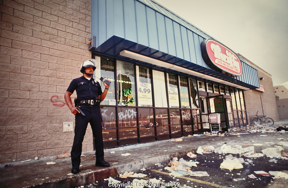 A lone LAPD officer stands guard outside a Thrifty Drug Store in South Central LA.