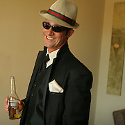 The brother of the bride chills out with a Corona, hat and sunglasses before departing for the ceremony.