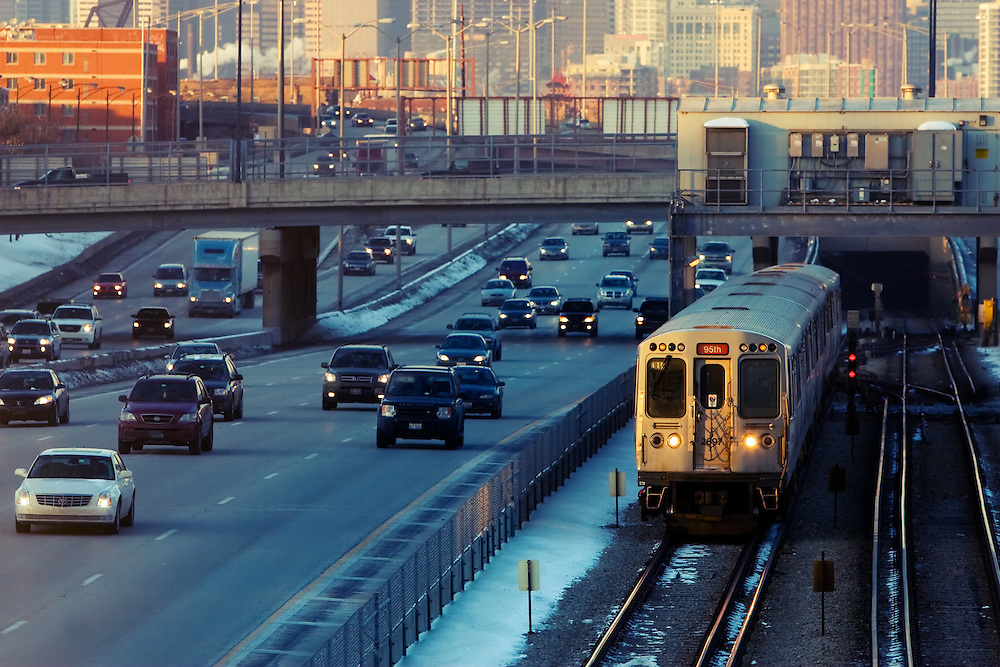 A Red Line L train exits the underground tunnel and pops out to do some 'between the interstate' running on the Dan Ryan expressway as rush hour commuter traffic on the parallel auto lanes begins to build.
