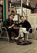 A couple hold hands while enjoying espresso at Caffe Trieste, North Beach, San Francisco, California, USA.