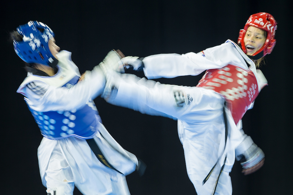 Adriana Martinez (R) of Venezuela tries to kick Doris Patino of Colombia in their 1/8 round contest against Adriana Martinez in the -57kg weight class of Taekwondo at the 2015 Pan American Games in Toronto, Canada, July 20,  2015.  AFP PHOTO/GEOFF ROBINS